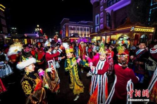 资料图:2019年12月31日晚,新疆乌鲁木齐市国际大巴扎,各族民众身着节日盛装,跳起麦西来甫,迎接2020年到来。中新社记者 刘新 摄