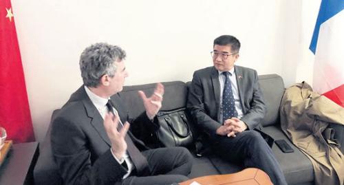 正在和客人商讨前往中国计划的周建防(右)。(《欧洲时报》/黄冠杰 摄)