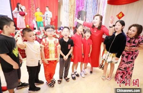 """图为晚会发起人和组织者王敏筠(右三)和张立霞(右一)给参加晚会的数十位小朋友发""""压岁""""红包。 林永传 摄"""