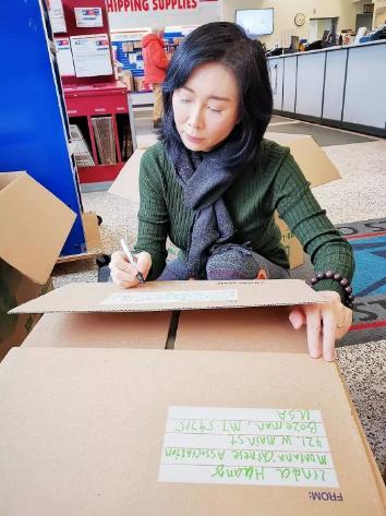 图为郑铮整理物资。图片来源:北京侨商会