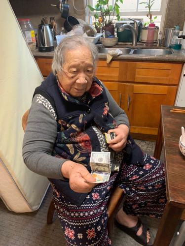 叶老太从钱夹掏出一百美金。(受访者供图)