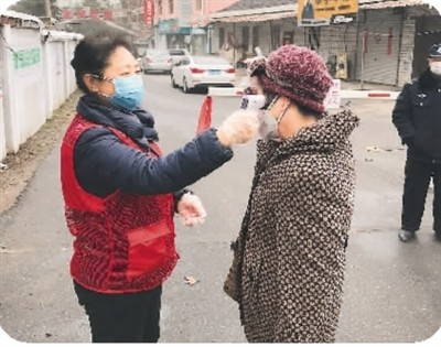 马丽(左)为居民测量体温。(马 丽供图)