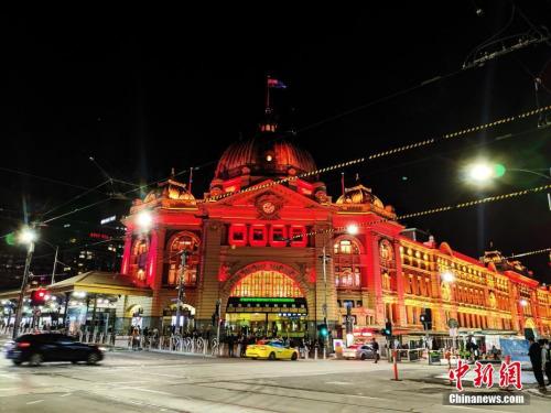 """当地时间2月21日晚,澳大利亚墨尔本的几处标志性建筑被中国红点亮,开启了维多利亚州政府""""休戚与共 (Stronger Together) """"支持华社活动,声援受新冠肺炎疫情冲击的华人社区。图为弗林德斯火车站亮灯。<a target='_blank' href='http://www.chinanews.com/'>中新社</a>发 卢紫嫣 摄"""