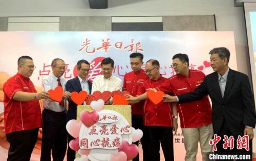 """马来西亚《光华日报》为支持中国抗击疫情举办的""""点亮爱心,同心抗疫""""义卖会。图为开幕仪式上,大家一同把""""爱心""""投进爱心箱。 陈悦 摄"""