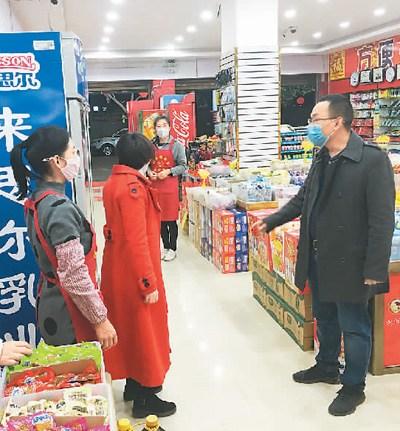 图为杨姚春(右)在云南省保山市龙陵县勐糯镇的一家超市了解商品库存情况。(李志锋摄)