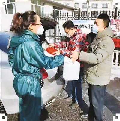 图为于洪(左一)正在接收吉林省通化市新阶联捐赠给通化市东昌区民主街江南社区的防疫物资。(于洪 供图)