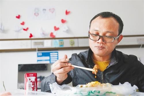 2月29日,在荆州市胸科医院,海南医疗队队员、儋州市人民医院心血管内科医生唐庆业开心地吃到了文昌鸡。本报特派记者 袁琛 摄