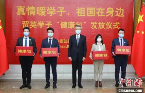 """资料图:中国驻英国大使刘晓明向中国留学生代表发放""""健康包""""。 任超 摄"""
