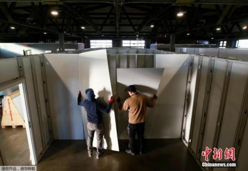 当地时间3月25日,德国希勒斯海姆,工作人员和志愿者将市政大厅改建为医疗中心用于收治新型冠状病毒患者。图为工作人员和志愿者在安装医疗中心隔间的墙面。