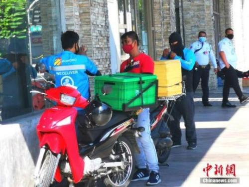 """当地时间4月4日,菲律宾首都马尼拉""""封城""""已20日,中小商家和餐厅基本关闭,快递小哥成为联通城市生活的主力。图为在马尼拉CBD马卡蒂绿带公寓外送快递的小哥。中新社记者 关向东 摄"""
