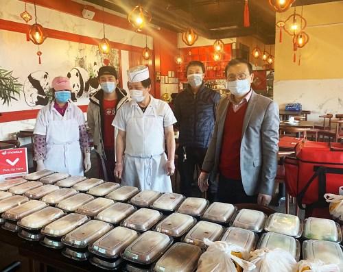图为胡晓军(右一)和会员们在准备外送免费餐饮。