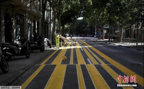 当地时间5月4日起,西班牙绝大部分地区进入分阶段降级封禁措施的准备阶段,部分小商铺重新开业。图为巴塞罗那街道上,工人们扩展人行道面积,以便利行人保持社交距离。