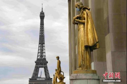 """法国于5月11日起逐步""""解封"""",为了提醒民众""""解封""""后注意防护,巴黎著名景点夏洛宫外的金色雕塑被戴上了口罩。(<a target='_blank' href='http://www.chinanews.com/'>中新社</a>记者 李洋 摄)"""