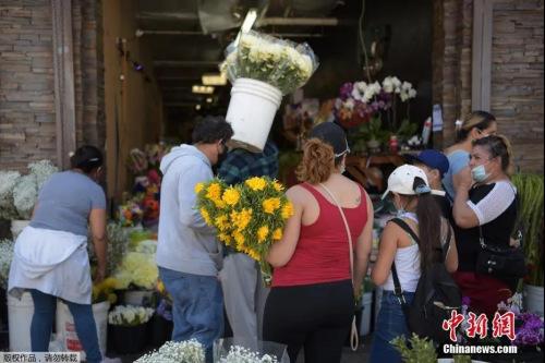 美国多地商店恢复营业,花市生意红火。当地时间5月8日,美国加利福尼亚州洛杉矶市,当地部分商业开始恢复营业,人们在洛杉矶花区购物。