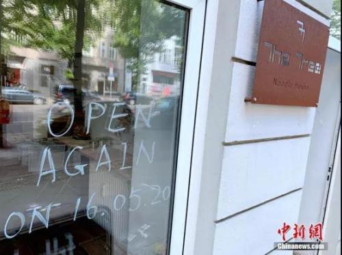 """5月15日,柏林米特区一家四川面馆在临街的落地窗写上了""""5月16日恢复营业""""的字样。<a target='_blank' href='http://www.chinanews.com/'>中新社</a>记者 彭大伟 摄"""