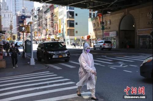 """资料图:5月12日,纽约市曼哈顿唐人街,一名""""全副武装""""的女子正在过马路。中新社记者 马德林 摄"""