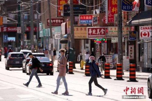 资料图:佩戴着口罩的行人穿行在加拿大多伦多中区唐人街。<a target='_blank' href='http://www.chinanews.com/'>中新社</a>记者 余瑞冬 摄
