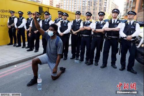 5月31日,英国伦敦的美国大使馆附近,一名抗议者在示威活动中单膝跪地。