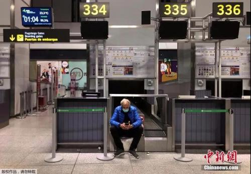 机场一名男子戴着口罩等待他的航班起飞。