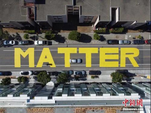 """当地时间6月13日,美国旧金山市政厅附近的街面上,出现用黄油漆涂写的巨幅""""Black Lives Matter""""(黑人的命也是命)字样。 中新社记者 刘关关 摄"""
