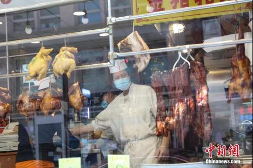 资料图:当地时间5月12日,纽约曼哈顿唐人街,一家恢复营业的烧腊店为人们提供外卖服务。中新社记者廖攀 摄