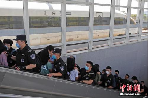 资料图:5月16日,上海黄浦公安民警在广东抓获犯罪嫌疑人并押解回上海。中新社记者 殷立勤 摄