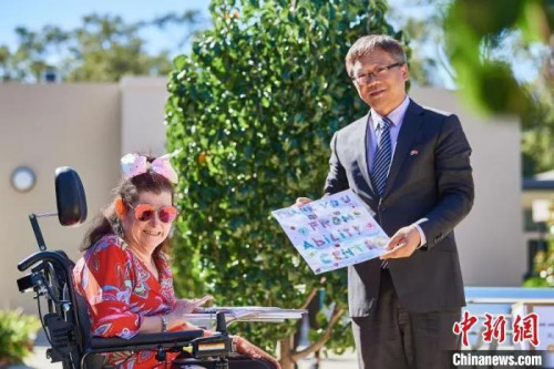 资料图:当地时间5月,孙晓轩接受残疾人服务中心居民代表Anita Jambanis 回赠画作。 Daniel Carson 摄