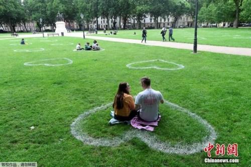 资料图:7月8日,英国布里斯托尔,艺术家在皇后广场的草地上画出心形图案,敦促人们保持社交距离。(<a target='_blank' href='http://www.chinanews.com/' >中新网</a>)