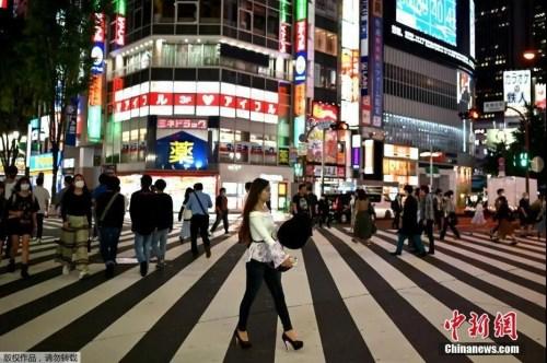资料图:5月15日,日本解除紧急事态宣言,人们穿过东京新宿区的一条街道。(<a target='_blank' href='http://www.chinanews.com/' >中新网</a>)