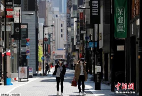 日本东京,戴口罩的女士走过空无一人的购物区。