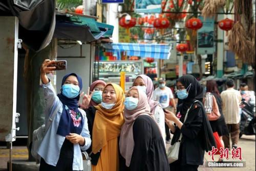 7月12日,因疫情暴发歇业的马来西亚吉隆坡茨厂街获准重新开业,图为马来西亚本地游客在茨厂街自拍。中新社记者 陈悦 摄