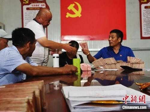 菏泽定陶区南城社区居民马利拿到了承包3个黑皮鸡枞菌大棚这一季的11万元分红。杨飞 摄