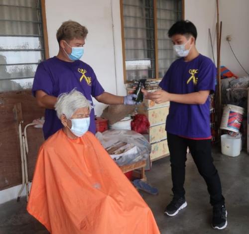 寇金来为社区长者免费剪发。(马来西亚《星洲日报》)