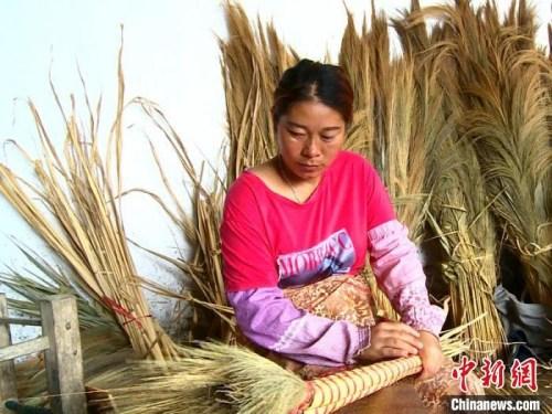 图为允哈村村民正在编制扫帚。昆明海关供图