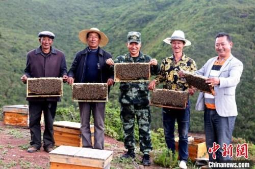 布哈与村民展示养蜂成果。图片由武警部队提供
