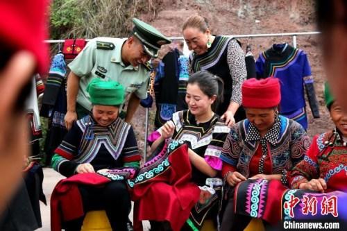 布哈带领村民发展彝绣产业。图片由武警部队提供