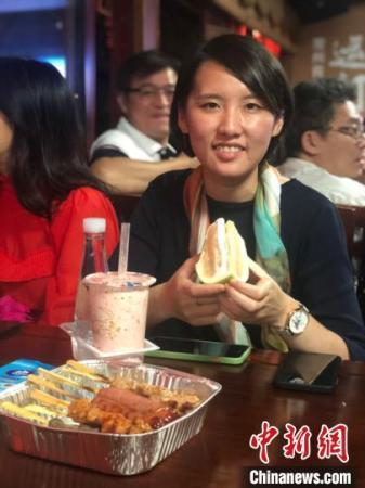 """王钰婷是一位来自台湾的""""90后"""",在常州吃着柚子和烤肉,她说,这里有家乡的味道。 唐娟 摄"""