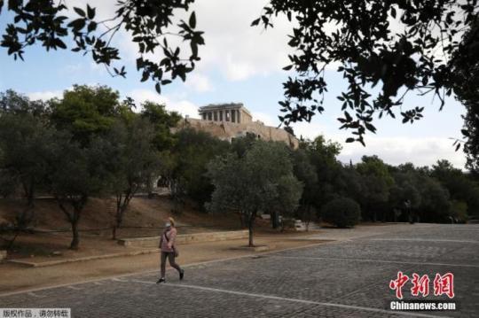 资料图:希腊雅典,一名戴口罩的女子经过帕特农神庙。