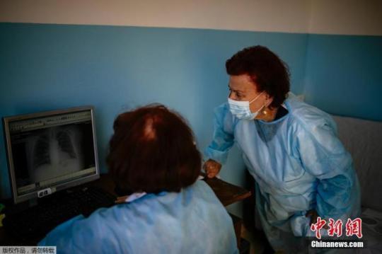 当地时间2021年1月20日,保加利亚,博戈耶娃医生正在与同事查看新冠患者的肺部X射线。