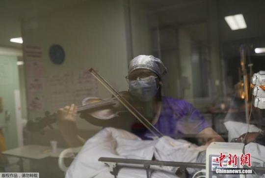 当地时间2020年7月9日,智利圣地亚哥,埃尔皮诺医院护士Damaris Silva为重症监护室内新冠肺炎患者演奏小提琴。