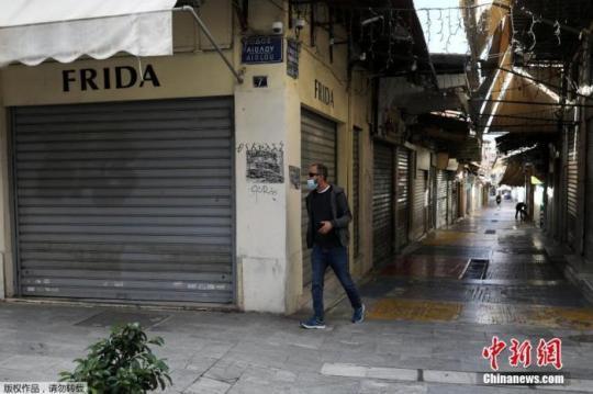 当地时间11月7日,希腊雅典,行人经过关闭的商业街。