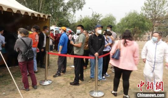 在现场排队等候接种疫苗的人们。 皇晓兵 摄