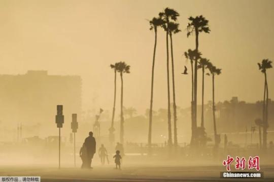 当地时间4月18日,美国加州海边大风卷起沙土,游客在漫天黄沙中出行。