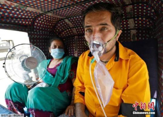 当地时间4月25日,印度一名患者和他的妻子在三轮车内等待进入医院接受治疗。