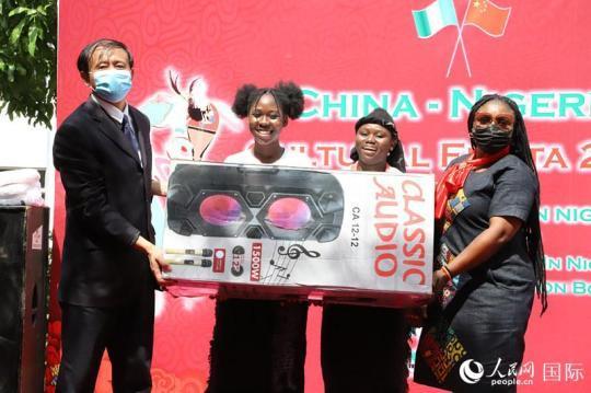 驻尼使馆文化参赞李旭大为获得尼日利亚传统舞蹈的贾碧中学颁发奖品。人民网记者 姜宣摄