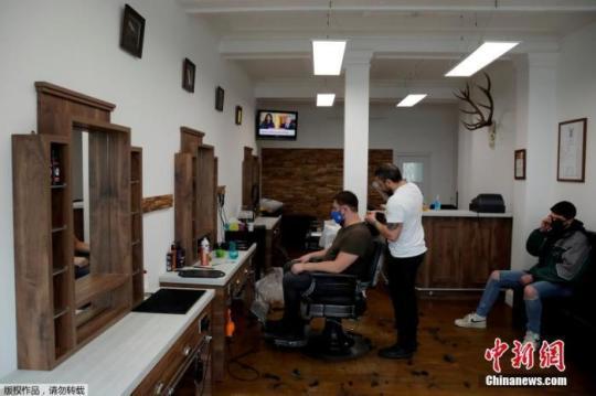 资料图:防疫限制逐步放宽,英格兰理发店恢复营业当地时间4月12日,英国赫特福德一家理发店内,理发师为顾客服务。