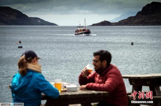 图为人们坐在酒吧外喝酒。