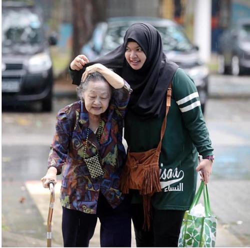 大马穆斯林女生用头巾为华裔老妇挡雨 网民点赞
