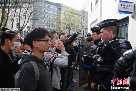 中国侨网资料图:当地时间3月26日晚,居住在法国巴黎19区的青田籍华人男子被破门而入的执法警察开枪打死。法新社报道称,首都巴黎的亚裔社区因此事举行示威抗议活动,并演变成暴力冲突。法国警方28日表示,他们逮捕了35名示威者。图为当地时间28日,在法国巴黎的亚裔民众在巴黎警察局门外与法国防暴警察对持。