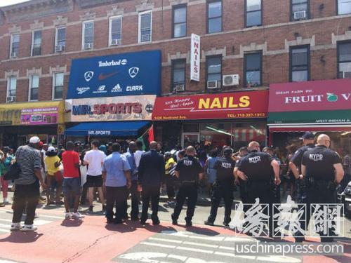 """中国侨网6日,大批美国非裔民众聚在""""新红苹果""""华人指甲店门前示威。 (美国《侨报》/崔国萁 摄)"""